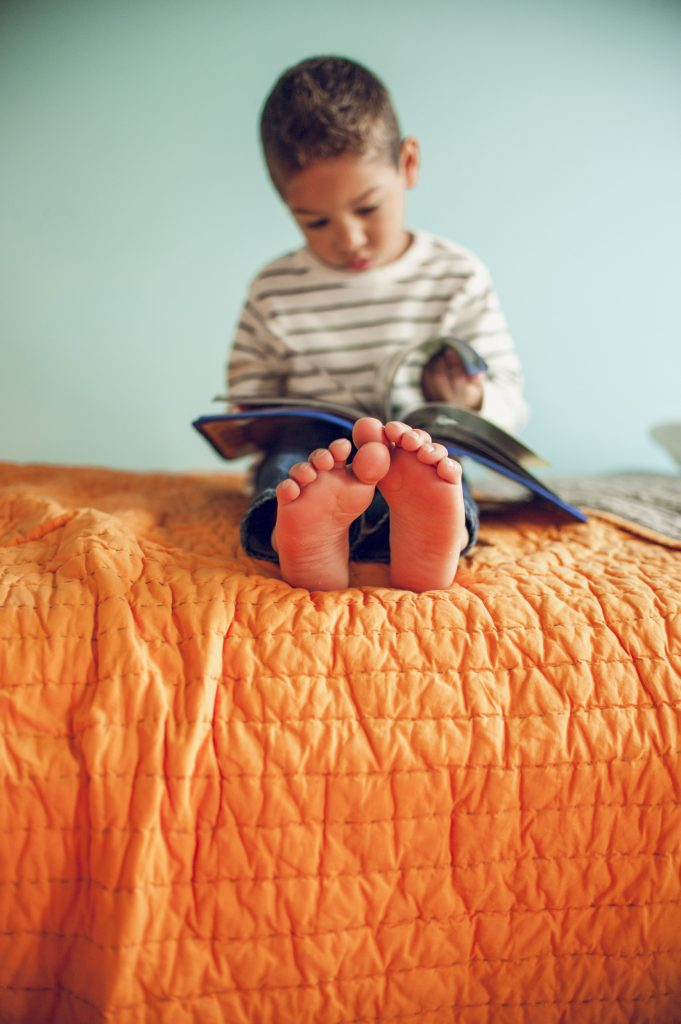 Detail image of little boy feet while he sits on bed reading a book.