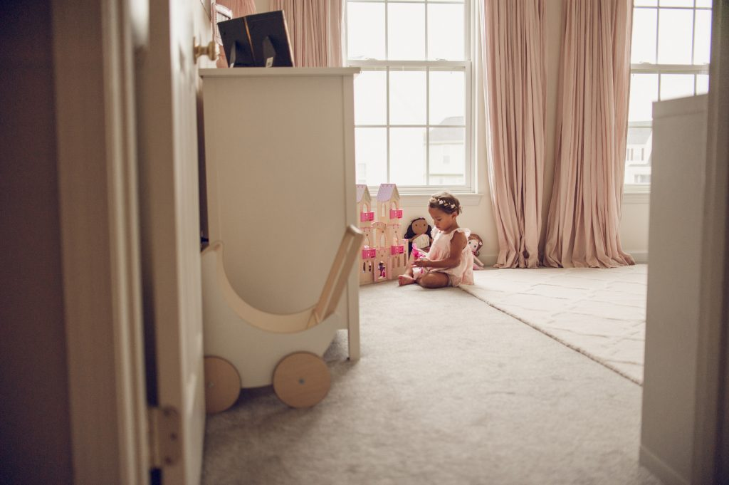 Image of little girl playing with her doll house.