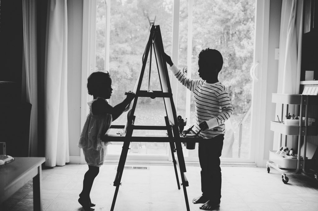 Black and white image of little boy and girl painting at art easel.