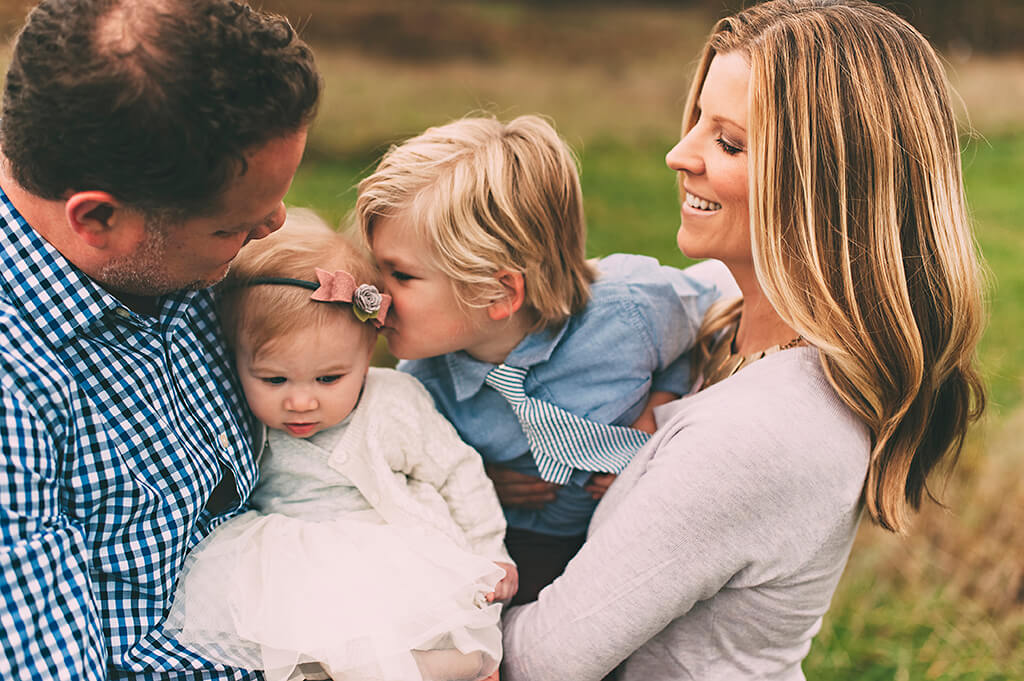Family of four in field near Cleveland with brother kissing sister on head.