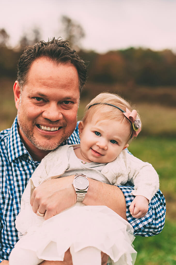 Dad holding daughter while smiling for family photographs.