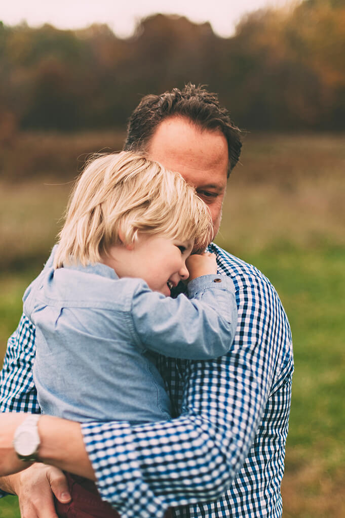 Son hugging his dad in a field in Medina, OH.