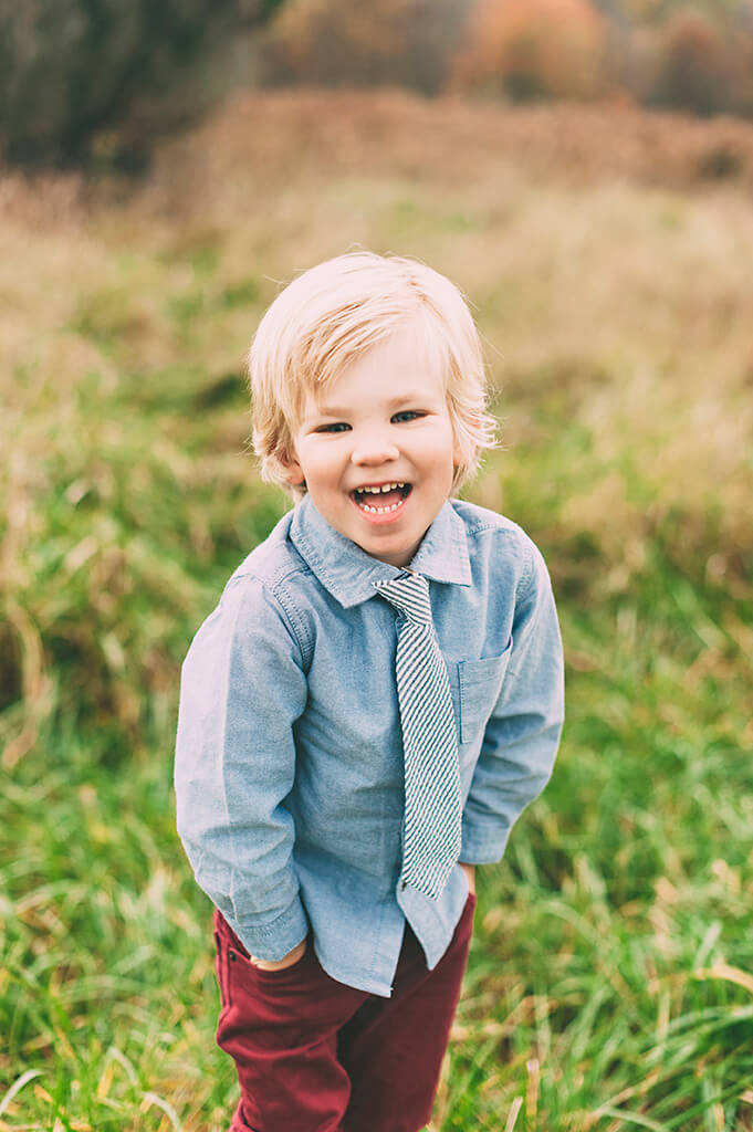 Little boy laughing during photo session in a field.