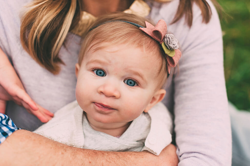 Little girl with blue eyes and wearing a bow headband.