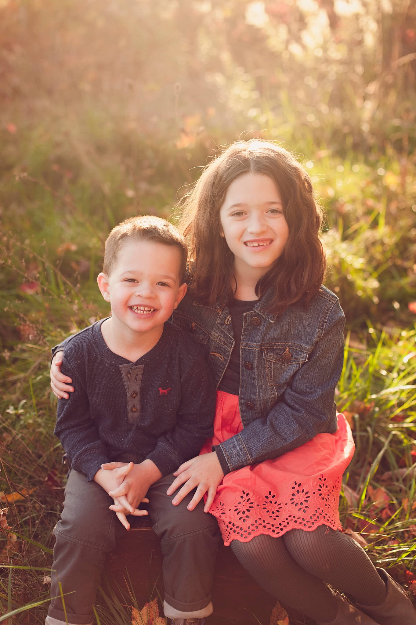 Sister and brother sitting in an Akron field for portrait at sunset.