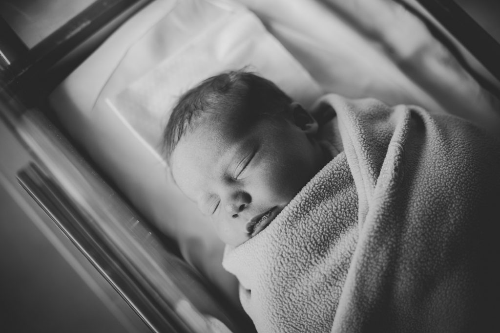 Black and white image of newborn baby girl in Cleveland hospital bassinet.