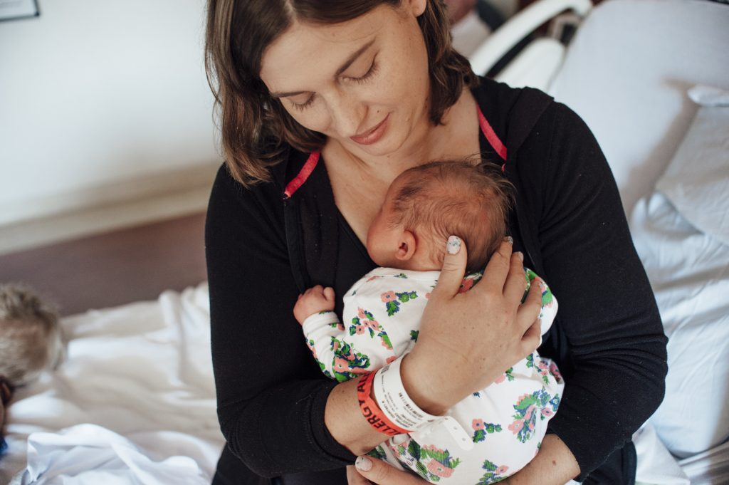 Mom holding new baby girl.