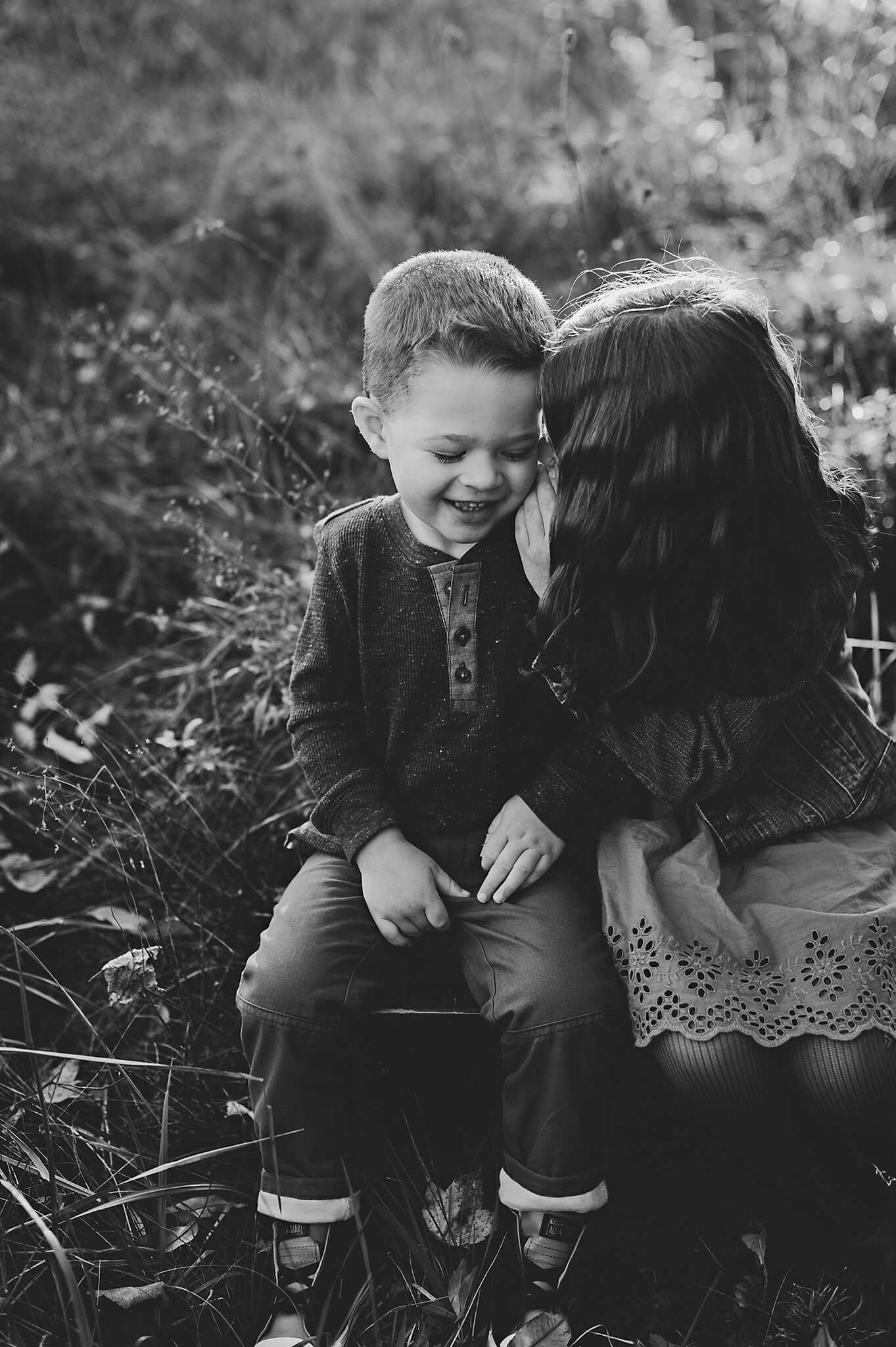 Black and white image of siblings whispering and laughing.