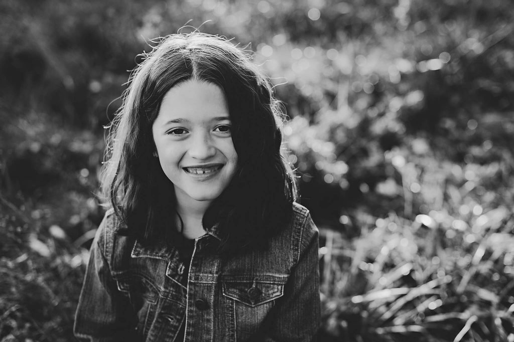 Black and white image of little girl smiling for portrait.