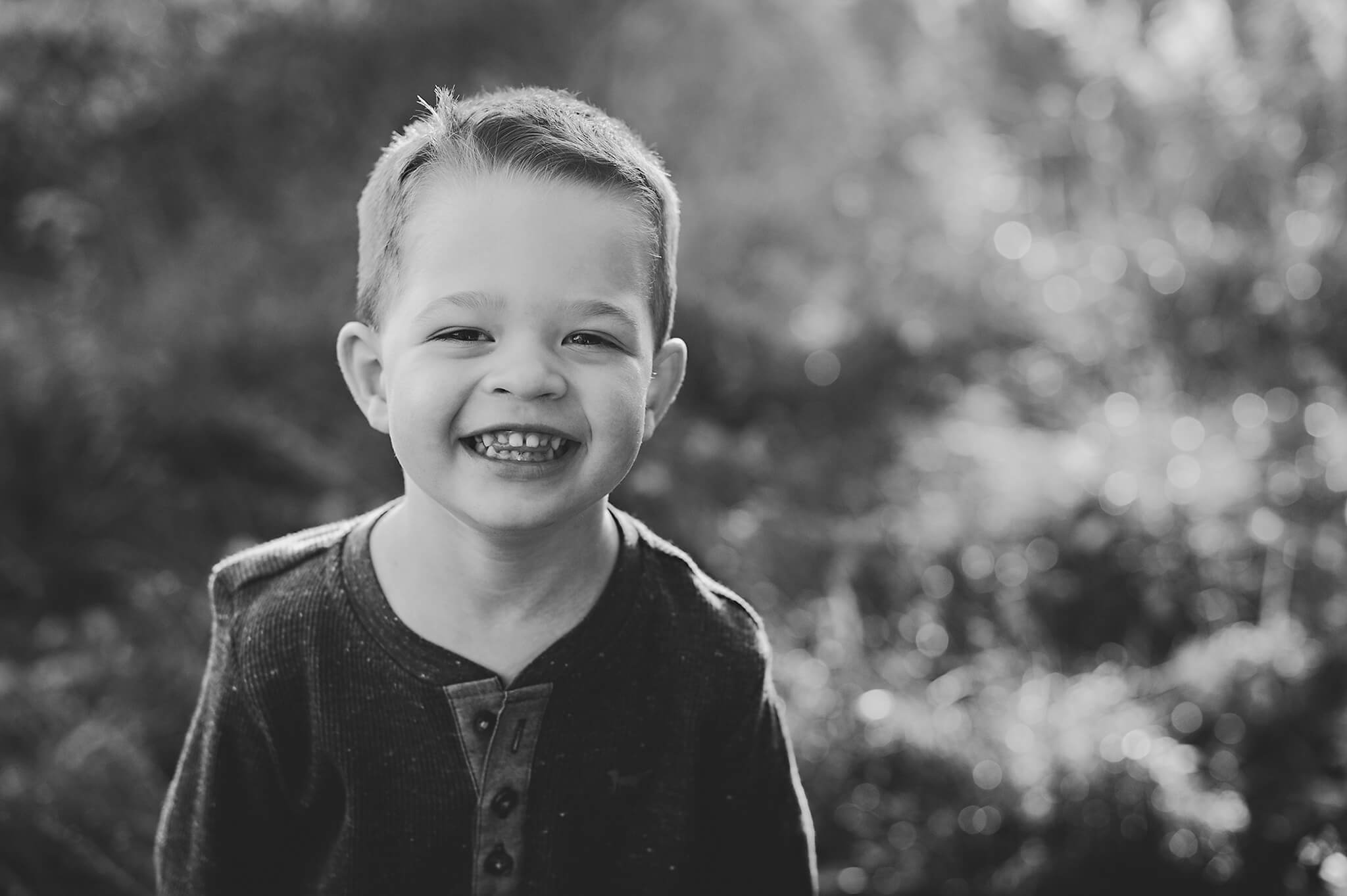 Little boy smiling in a black and white image for family portrait.