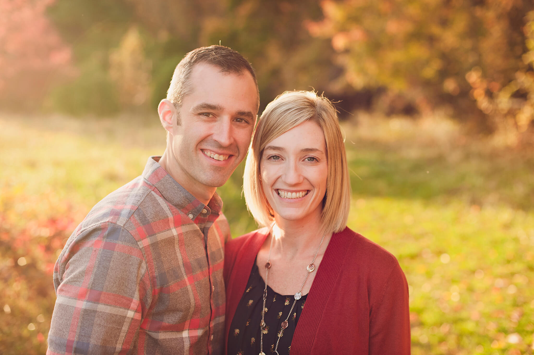 Image of couple smiling for photos in Akron, OH park.
