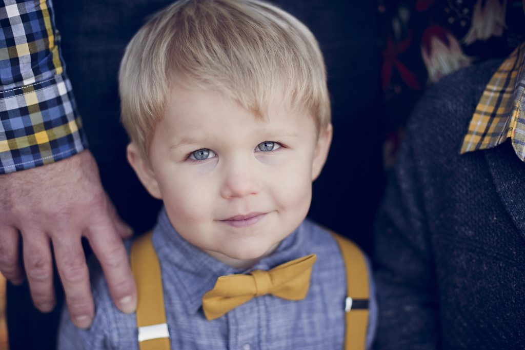 Blonde hair blue eyed boy wearing suspenders during family photo session.