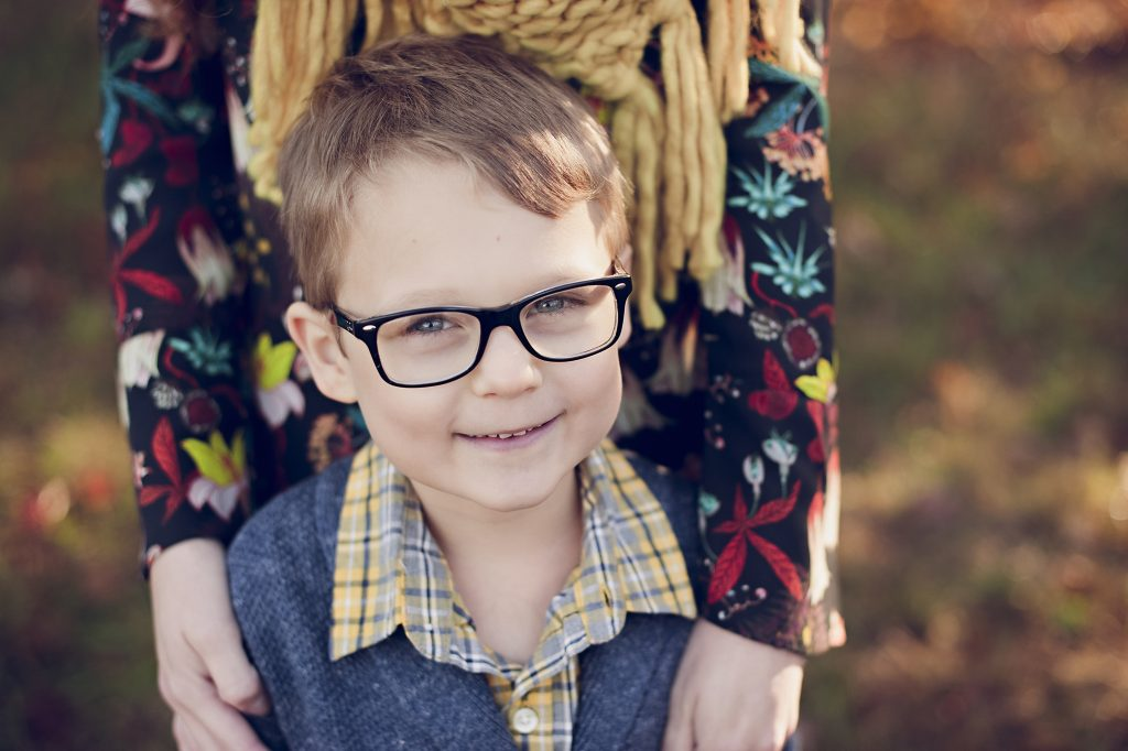 Little boy wearing glasses standing with mom for family photos.
