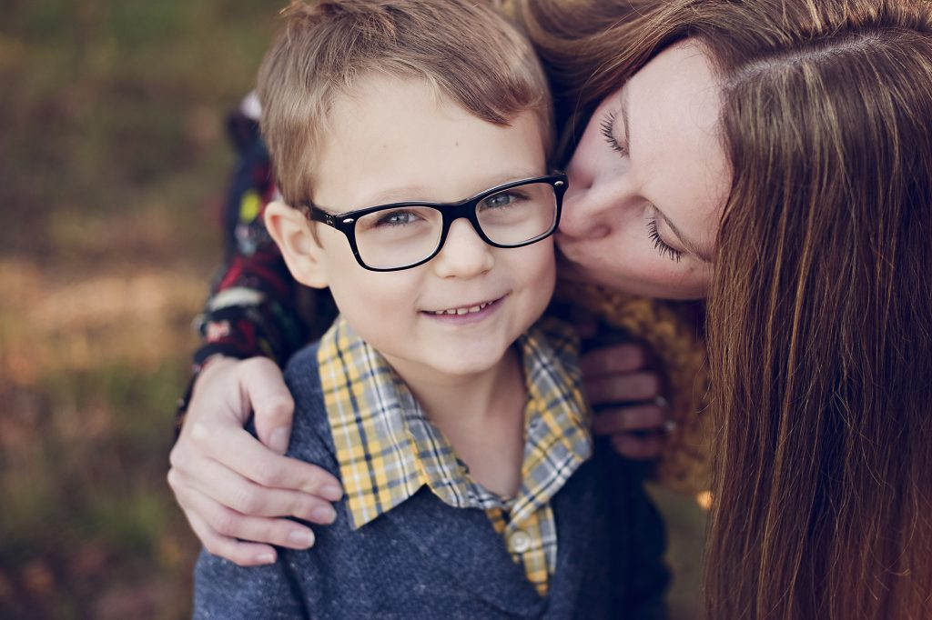 Mom giving son kiss the cheek during Cleveland family photo session.