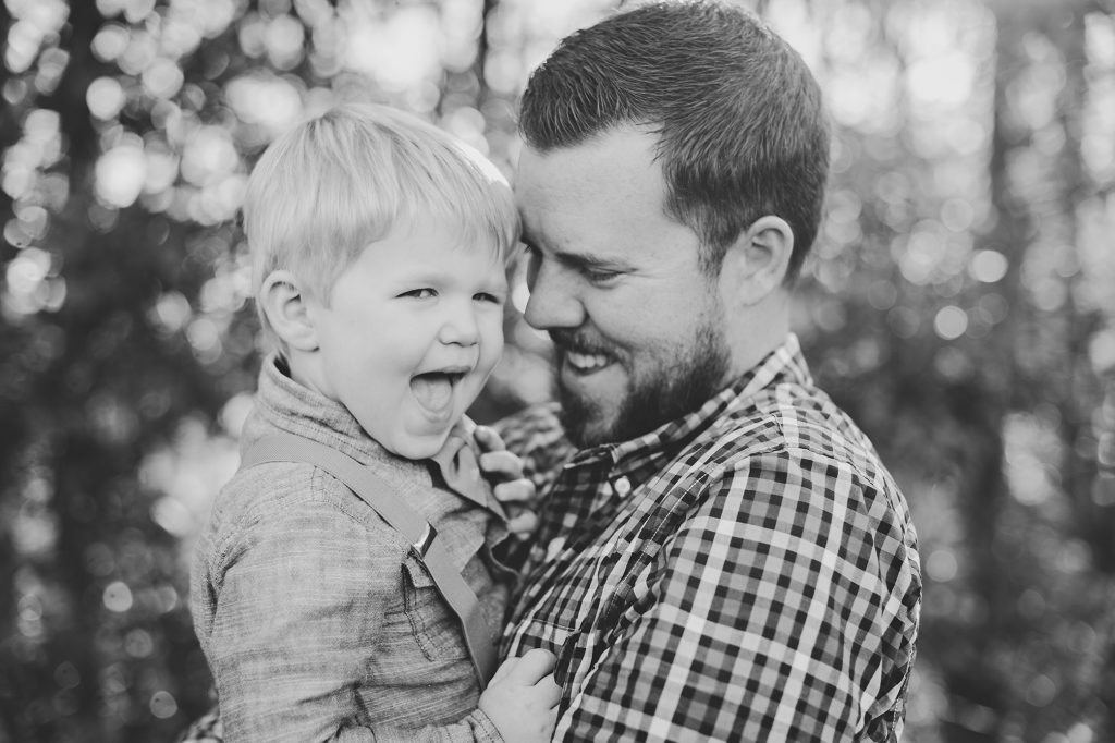 Black and white image of dad and son laughing during family photos.