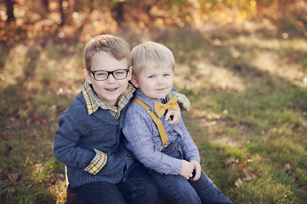 Two young brothers sitting on box during family photos in Medina, OH.