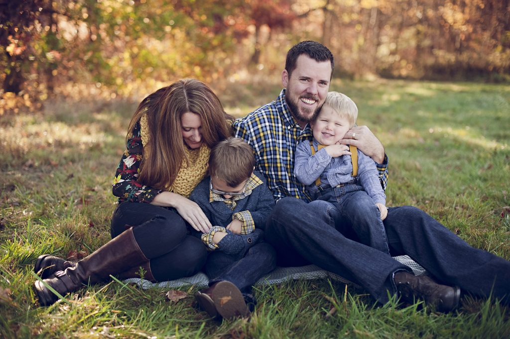 Family snuggling in field during fall family outdoor photos.