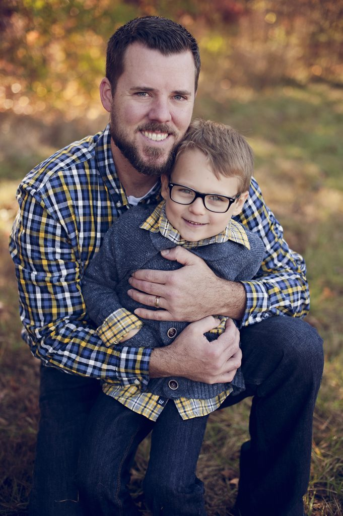 Dad giving son hug and smiling for family portraits near Cleveland.