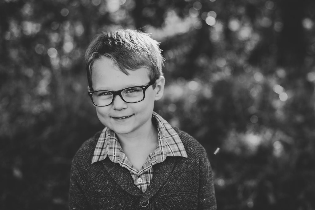 Black and white image of little boy in glasses during family photos outdoors in the fall.