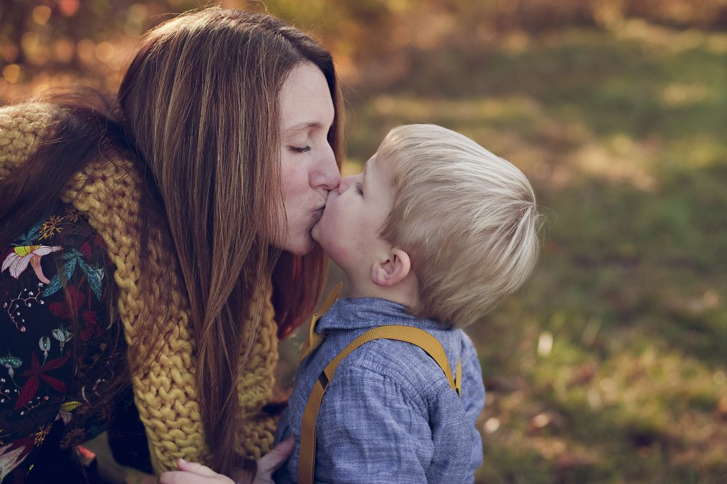 Mom and son giving kiss during family photos in Medina.