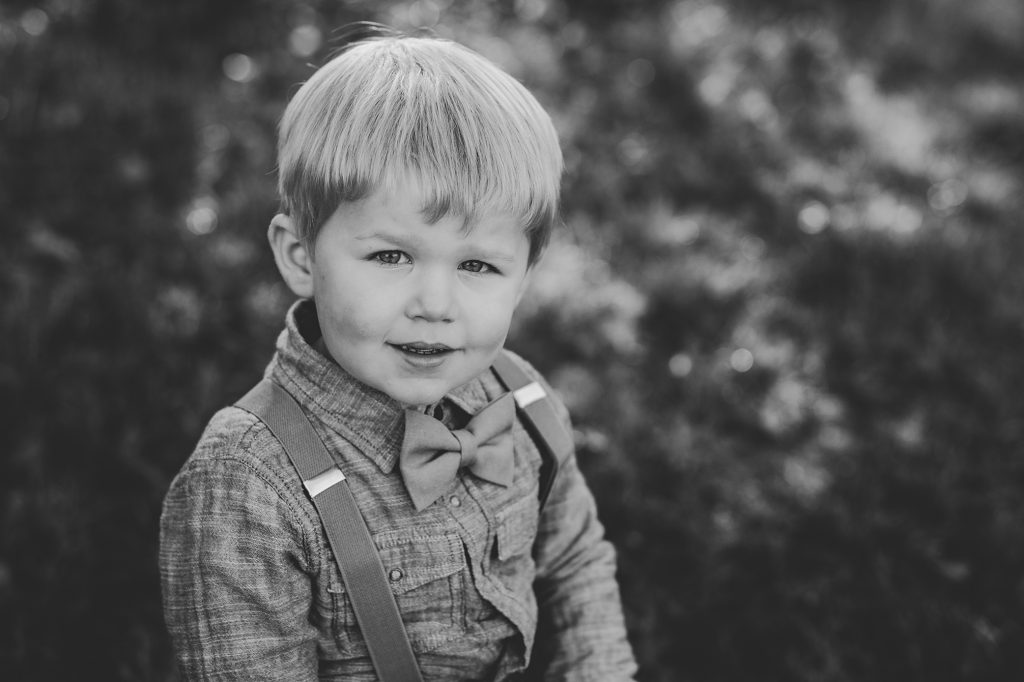 Black and white image of young blonde boy in suspenders.
