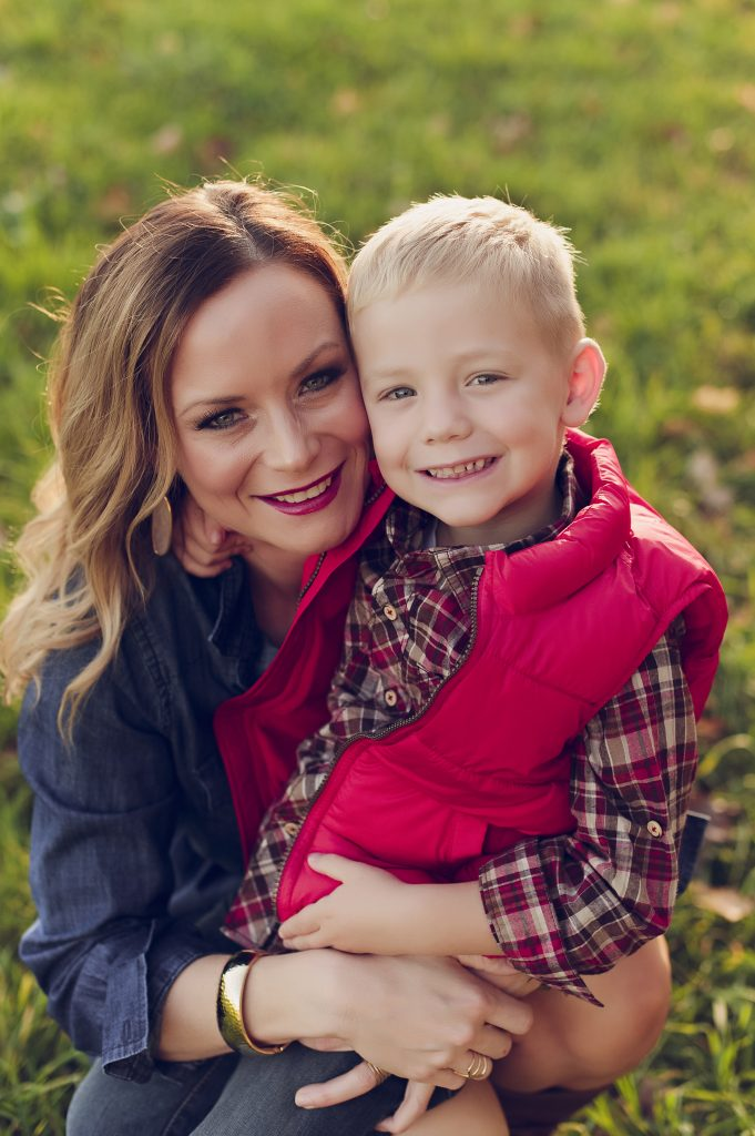 Mom with blonde boy wearing red vest smiling for outdoor portrait session.