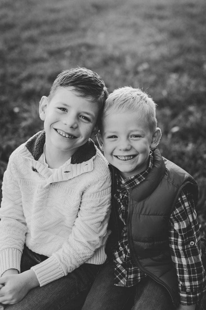 Black and white image taken by Molly Watson, a Cleveland Photographer, of two brother outdoors in a field.