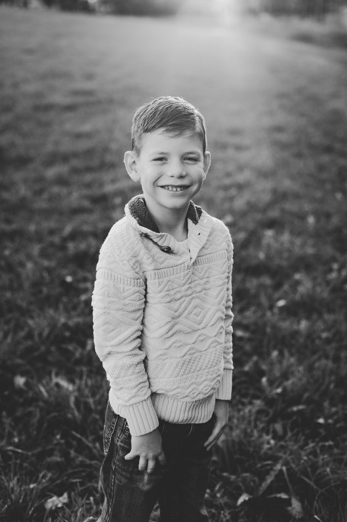 Black and white image of young boy smiling for outdoor family photo.