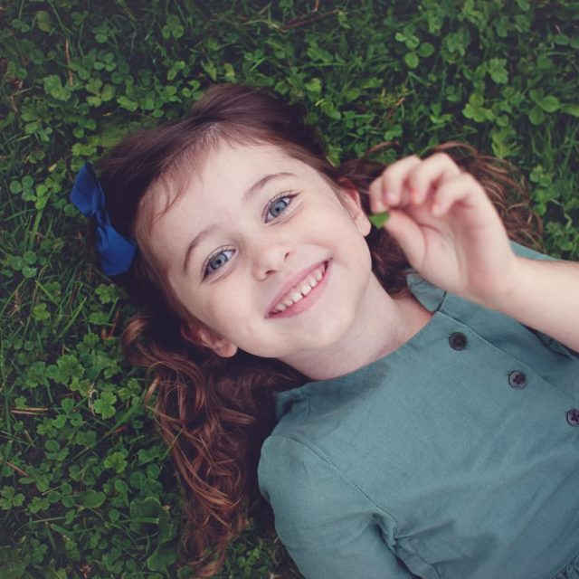 Little girl in green dress laying in the grass.