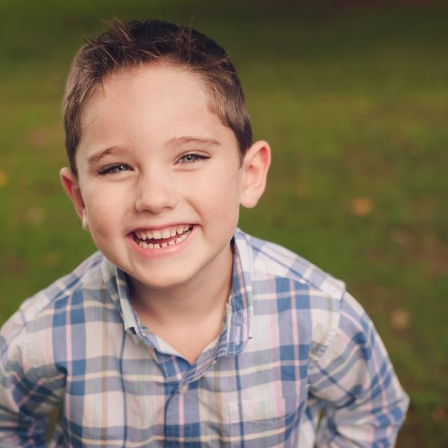 Little boy in blue plaid shirt smiling for portrait in Canton, OH.