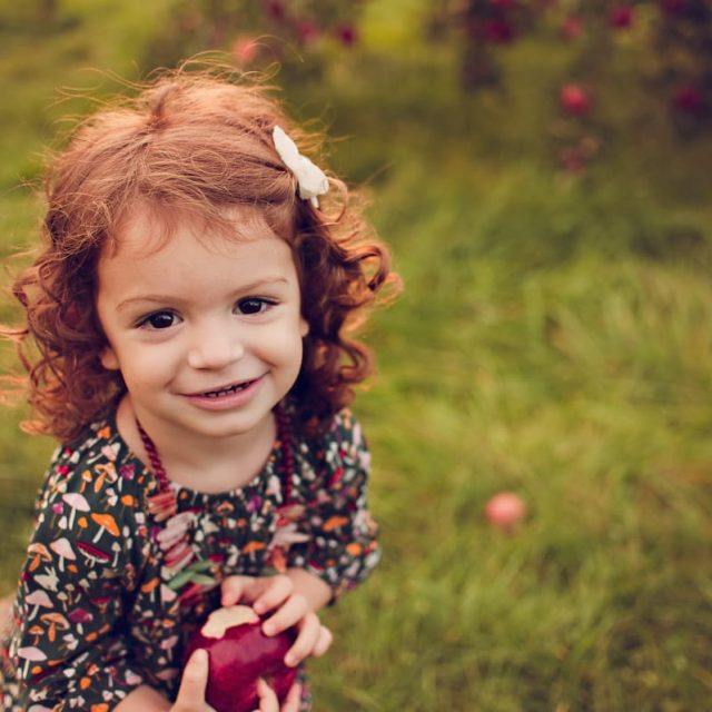Little girl smiling holding apple at Geig's Apple Orchard.