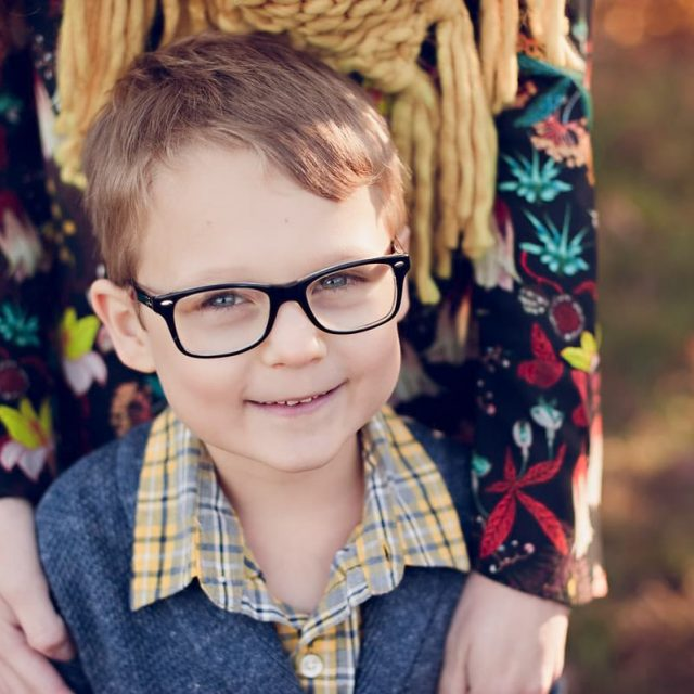 Boy wearing glasses with mother for family photos in field near Cleveland.