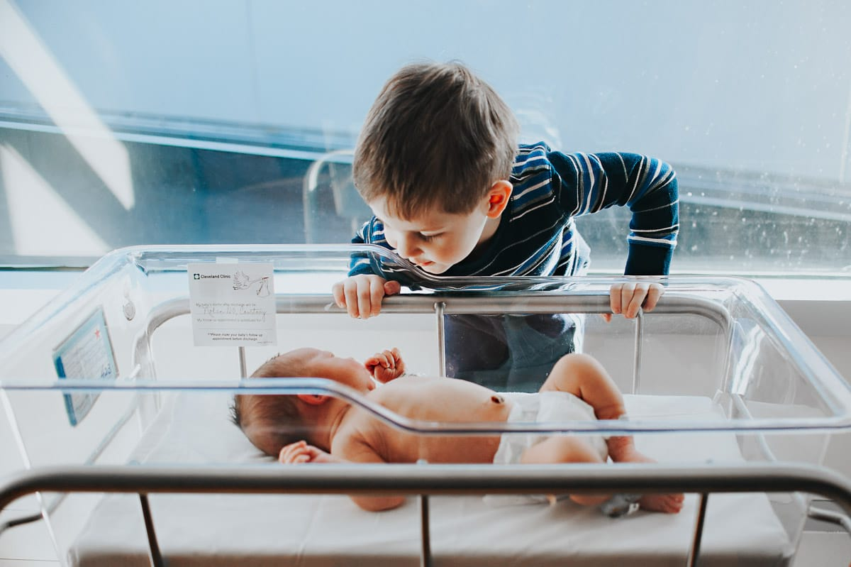 Big brother looking at baby brother in Cleveland hospital bassinet.