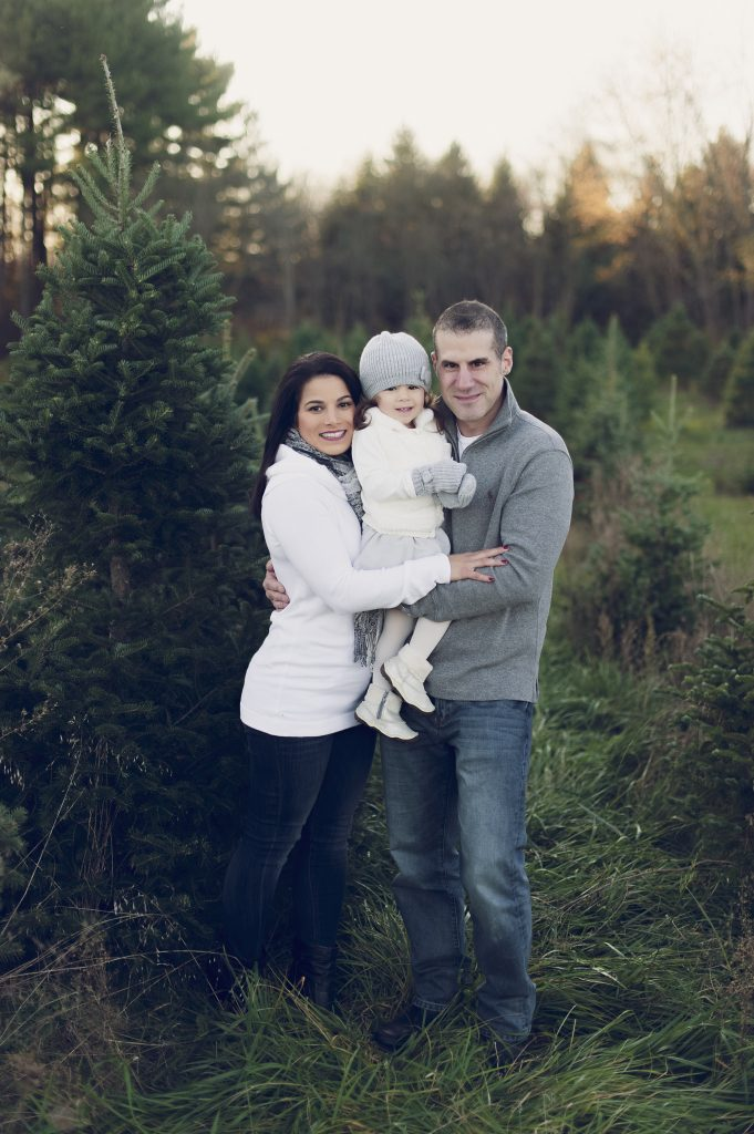 Family of three at tree farm near Cleveland, OH for family photos.
