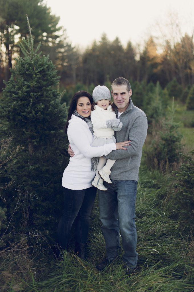 Family of three at tree farm near Cleveland, OH for family photos.