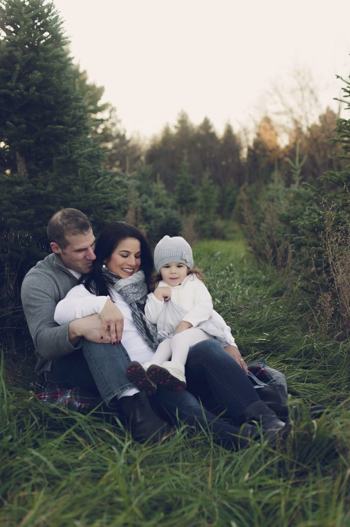 Mom, dad and daughter sitting at Cleveland, OH Christmas tree farm for family holiday photos.