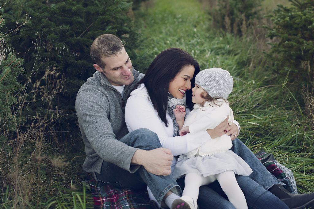Dad, mom and daughter sitting on blanket outdoor at Christmas tree farm.