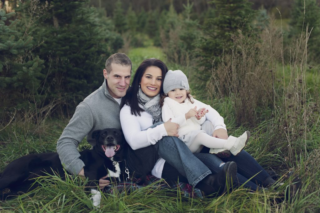 Family with dog smiling for family portrait at Cleveland tree farm.