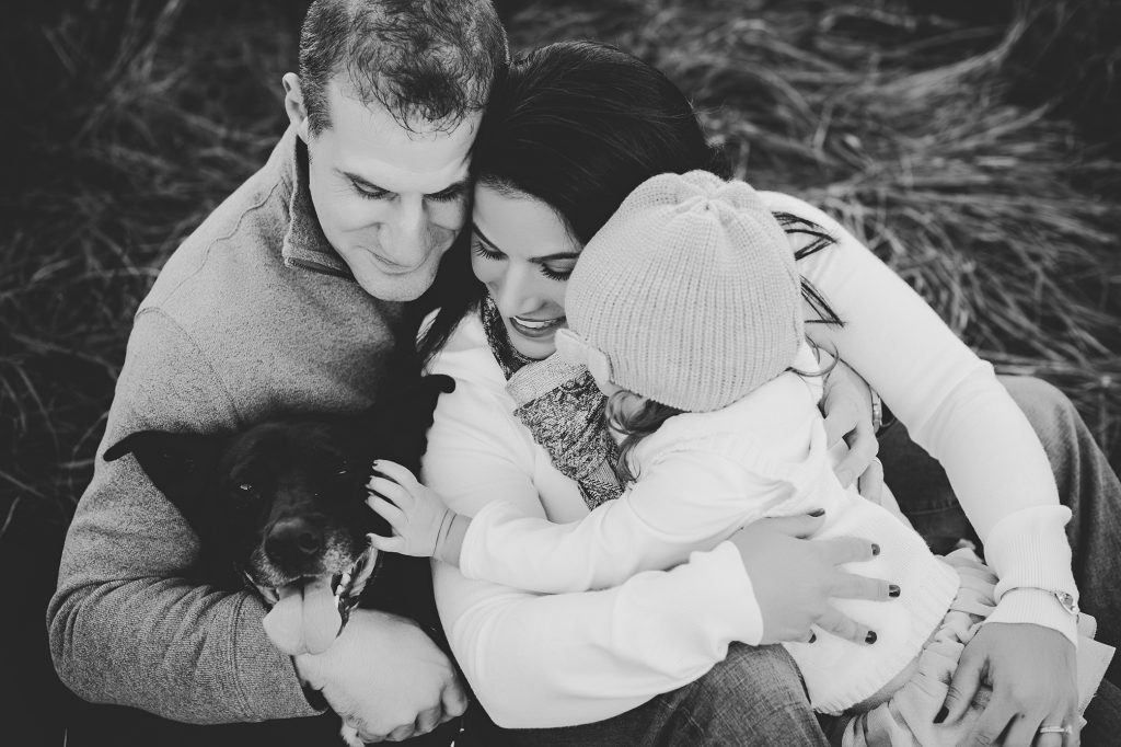 Black and white image of family of three with little girl petting dog.