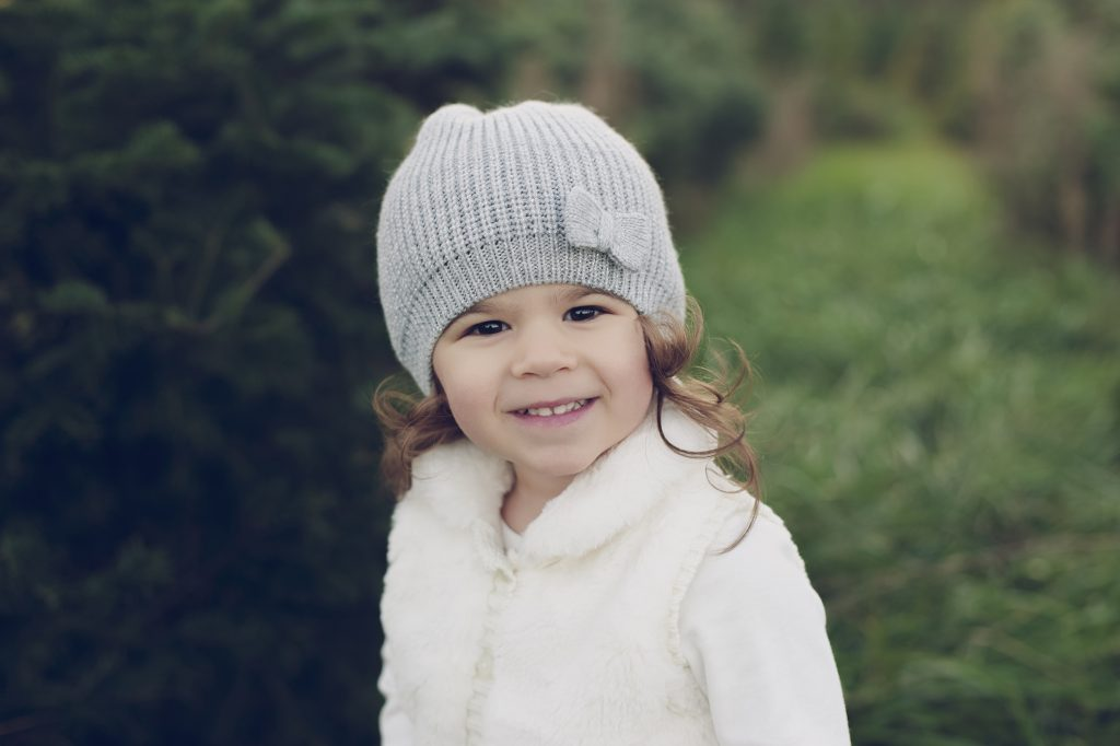 Little girl wearing snow hat smiling for portrait at tree farm near Cleveland.