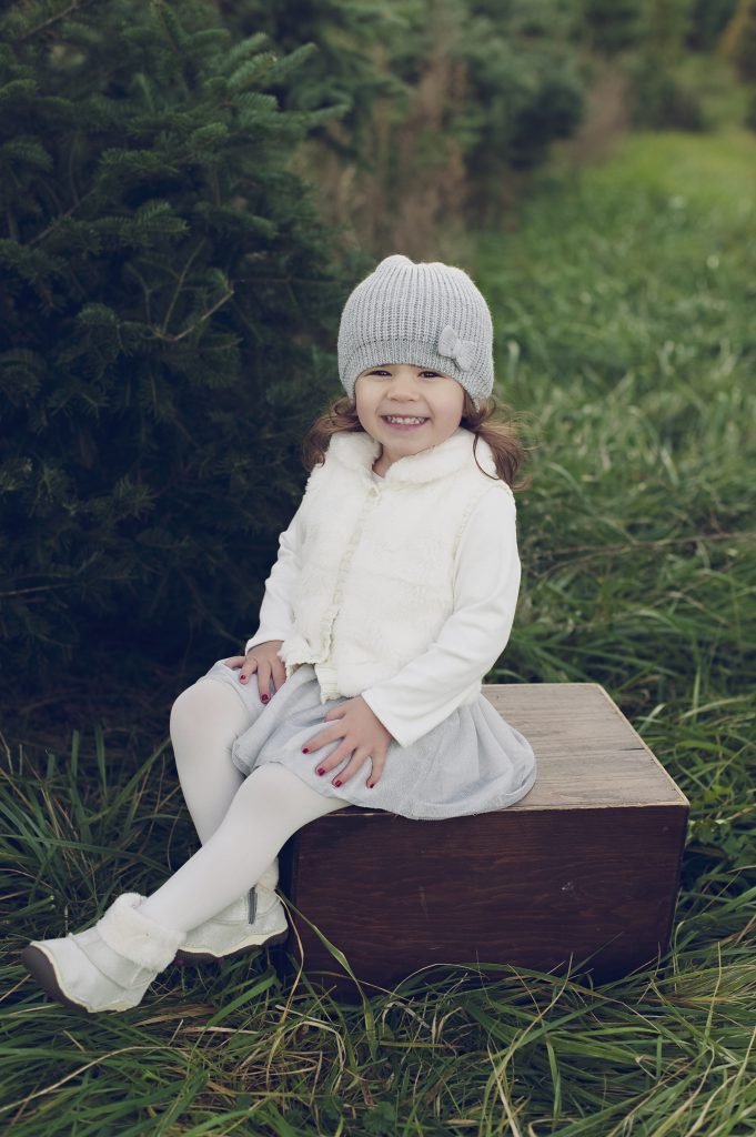 Little girl sitting on wooden box at tree farm near Cleveland.