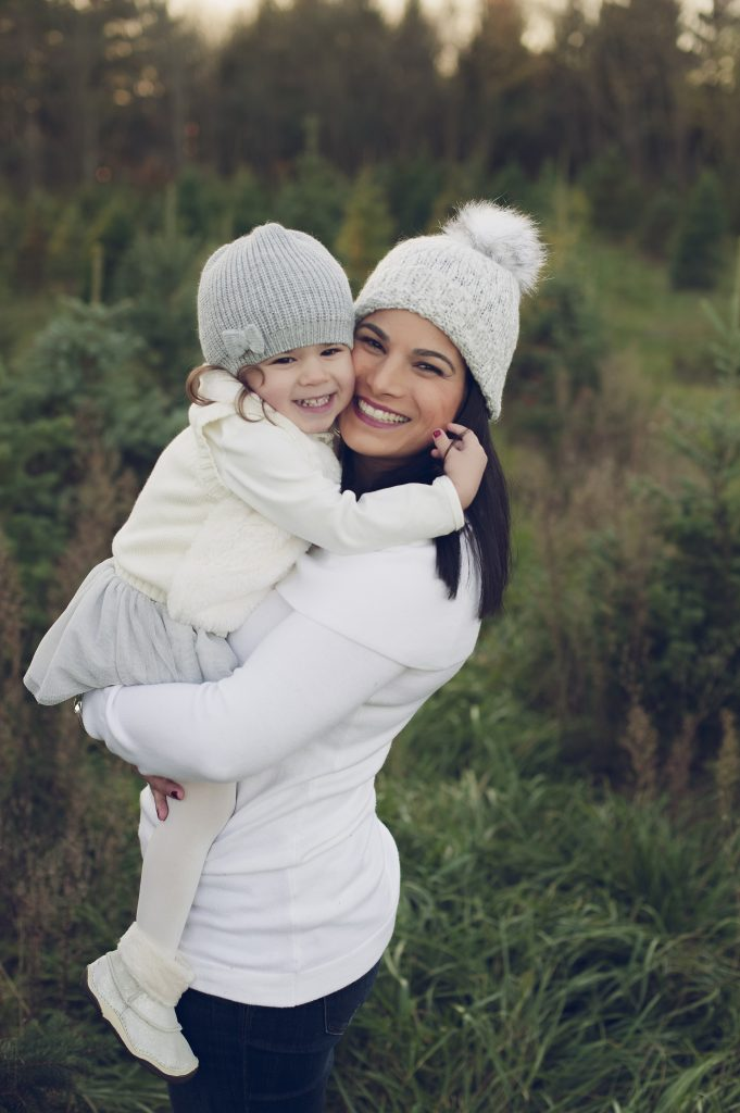 Mom and daughter smiling for portrait at Christmas tree farm for holiday family photos.