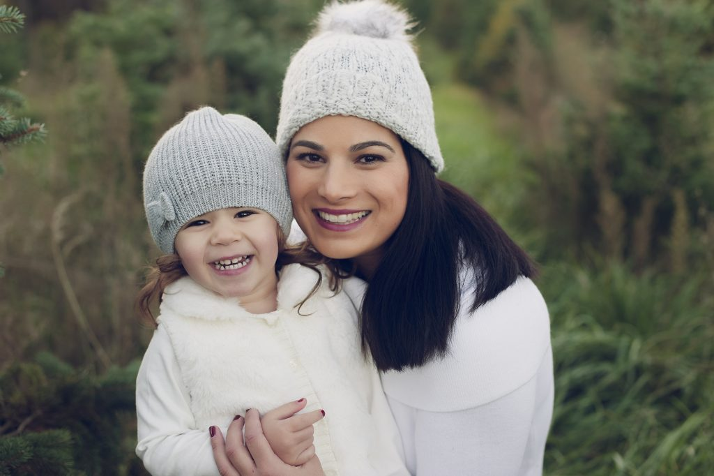 Little girl and her mom wearing winter hats outdoors at tree farm.