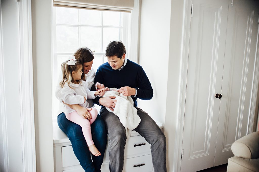 Family of four sitting on nursery window seat looking at new baby girl.
