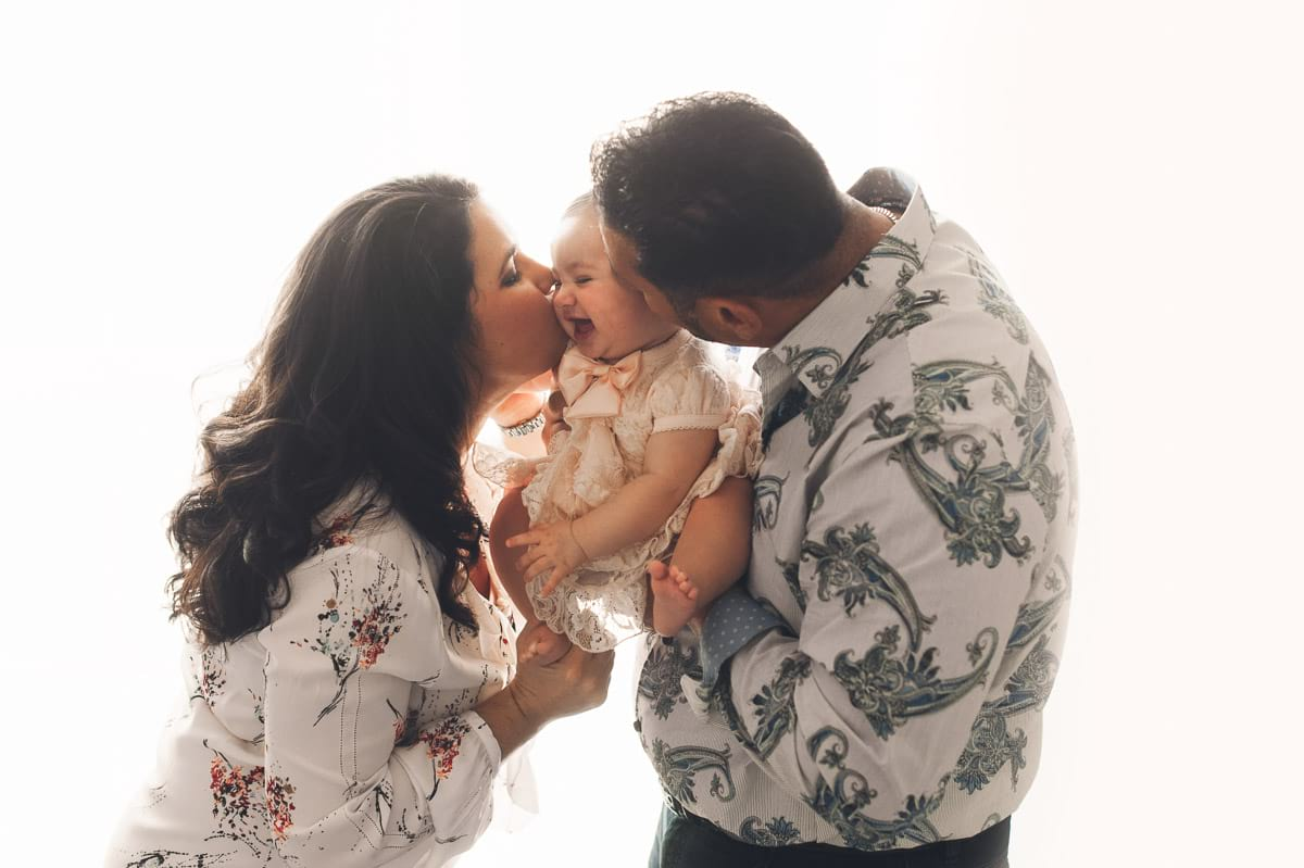 Parents giving baby daughter a kiss in Medina photography studio.