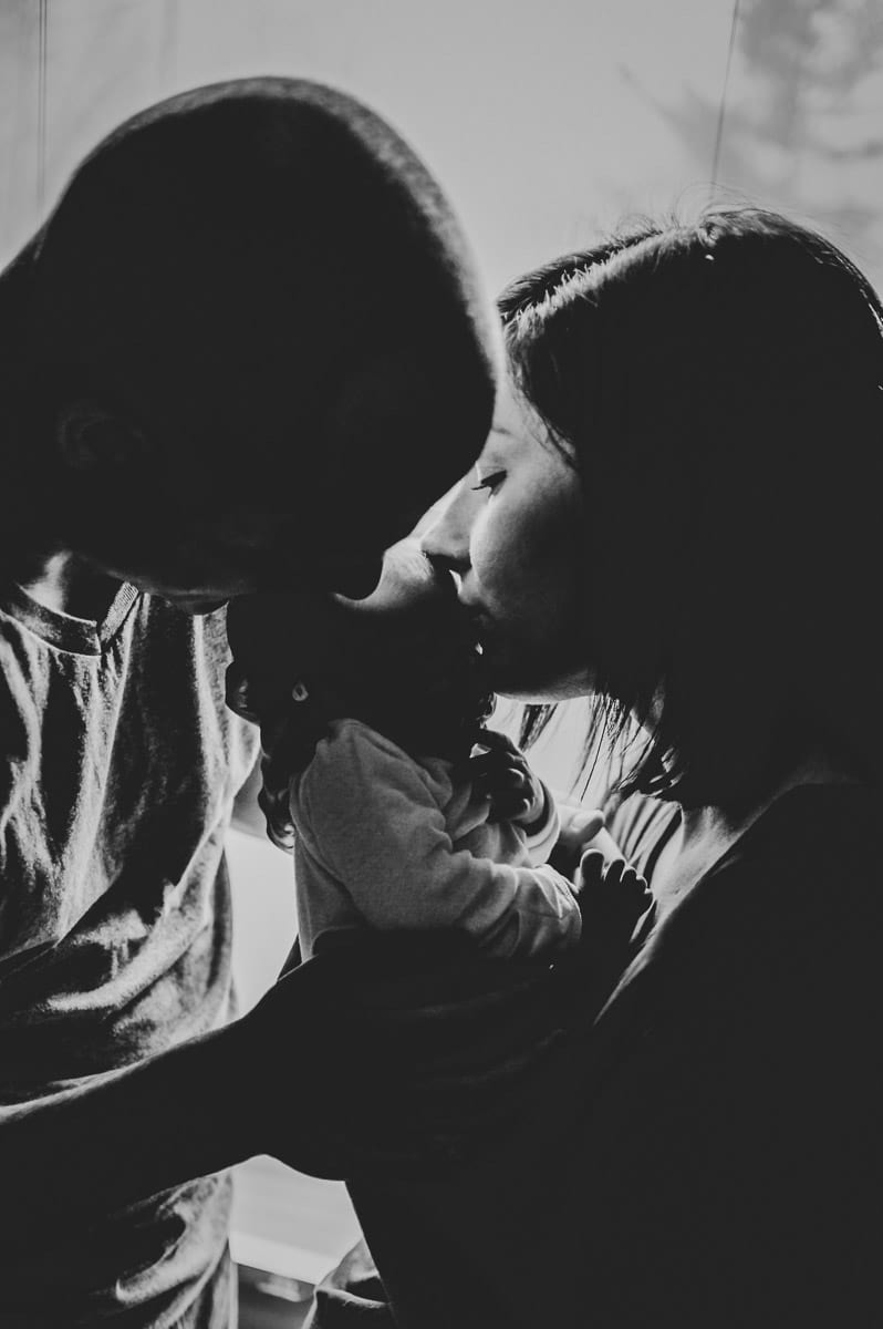 Black and white of parents kissing baby boy.