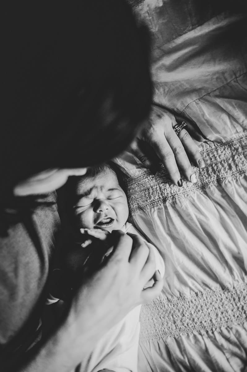 Black and white photo of mom comforting crying baby on bed.