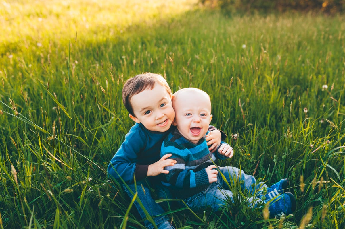 Brothers laughing and sitting in the grass in a Medina field.