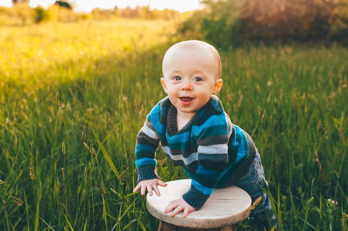 Baby boy standing at a stool smiling for photos.