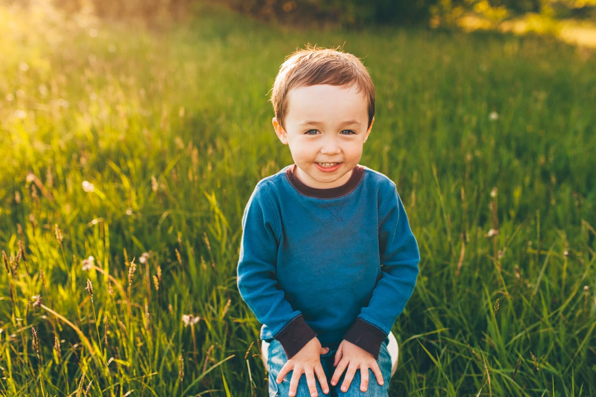 Adorable little boy sitting for photos at sunset in a field.